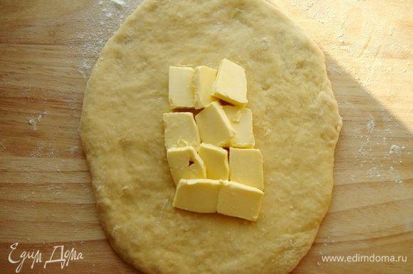 Раскатать тесто в пласт,в середину положить сливочное масло кусочками.