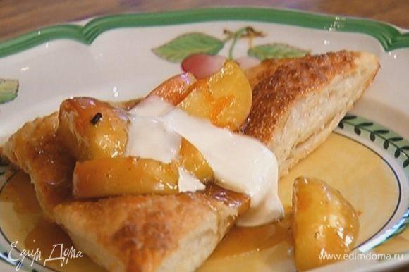 На выпеченные треугольники выложить яблоки с соусом и полить сметанным кремом.