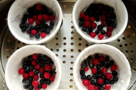 Жаропрочные формочки застелить пищевой плёнкой, а лучше смазать маслом. В каждую форму положить по горсти ягод (у меня черника и клюква).