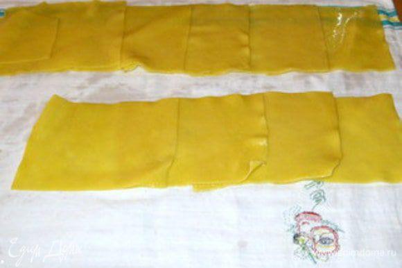 Накрыть рабочую поверхность кухонным полотенцем. Разложить на полотенце прямоугольники из пасты, накладывая один на другой по нескольку в ряд.