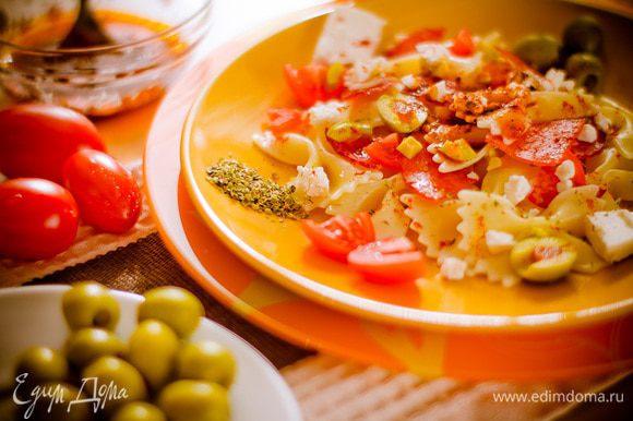Фету разломите руками, оливки разрежьте пополам. Смешайте бантики с кусочками салями, дольками помидоров и оливками. Приготовьте соус: смешайте оливковое масло, молотую паприку, орегано, соль и перец. Залейте салат соусом и слегка перемешайте. Сверху посыпьте фетой.