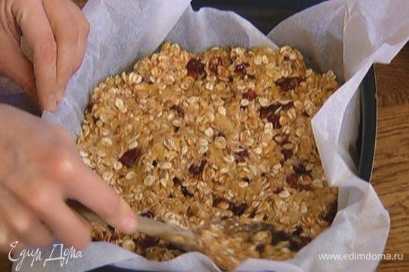 Форму выстелить бумагой для выпечки, выложить овсяное тесто, разровнять и отправить в разогретую духовку на 15 минут.