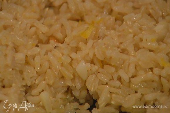 Выложить в сковороду с чесноком рис, влить оставшееся оливковое масло, перемешать.