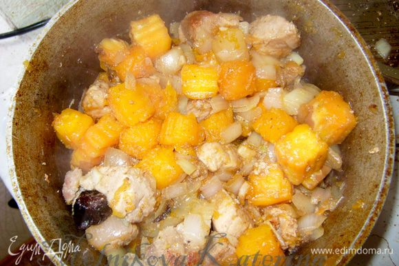 Добавить к мясу лук, тыкву, чеснок и тушить 7-10 минут.