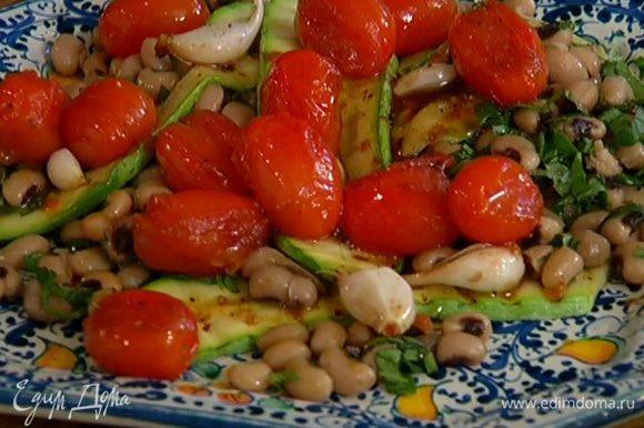 Выложить фасоль на тарелку, сверху разложить цукини и помидоры с чесноком. Полить соком, оставшимся в противне от помидоров.