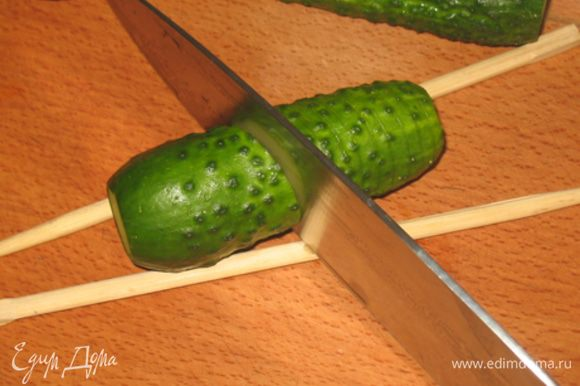 Между двух китайских палочек кладем огурец и делаем разрезы под 45 градусов. переворачиваем огурец на 180 градусов, вдоль длиной стороны повторяем надрезы, нож в туже сторону.