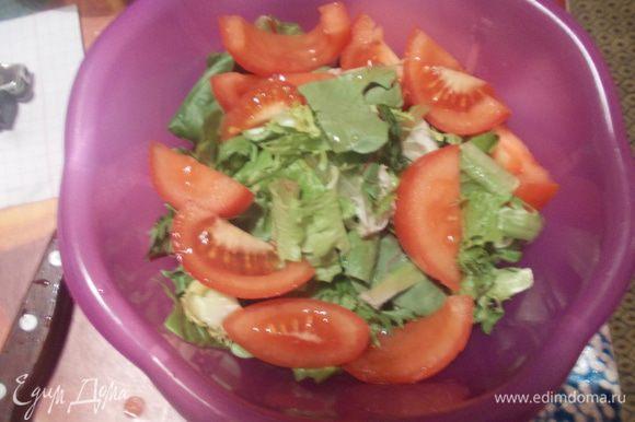 Листья салата промыть, обсушить и выложить в салатницу, добавить нарезанный дольками помидор, сбрызнуть оливковым маслом и соком лимона.