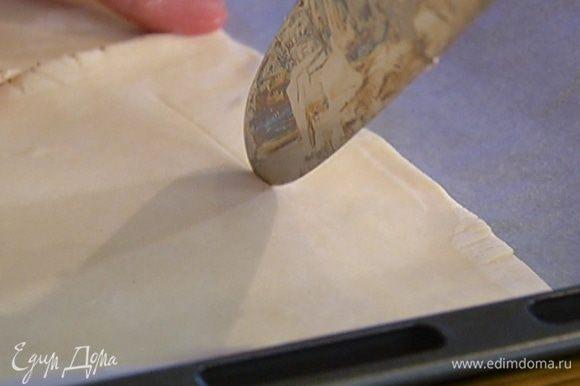 Противень выстелить бумагой для выпечки, выложить тесто и на каждом пласте, отступая на 2 см от края, ножом прочертить квадрат, не прорезая тесто до конца, чтобы получились бортики.