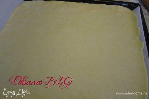 Противень застелить пергаментной бумагой. тесто разделить на 2 части 1 больше вторую меньше. Большую часть раскатать и выложить на противень.