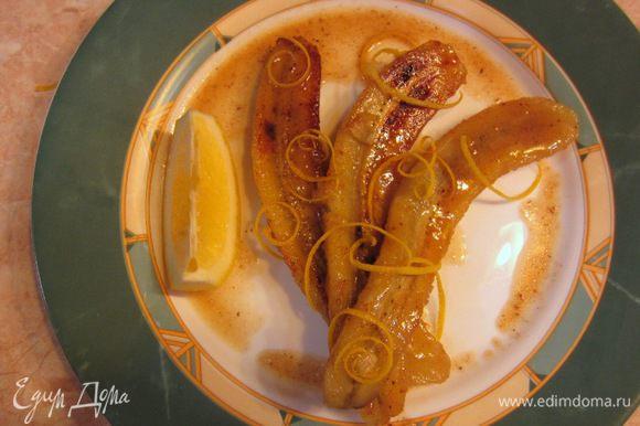 Через пару минут выложите бананы в тарелку. Долейте в сковороду вторую порцию спиртного и уварите соус пополам. Процедите соус через сито. Полейте сверху на бананы. Снимите немного цедры с лимона (я это делал специальным ножом). Выложите к бананом дольку лимона.