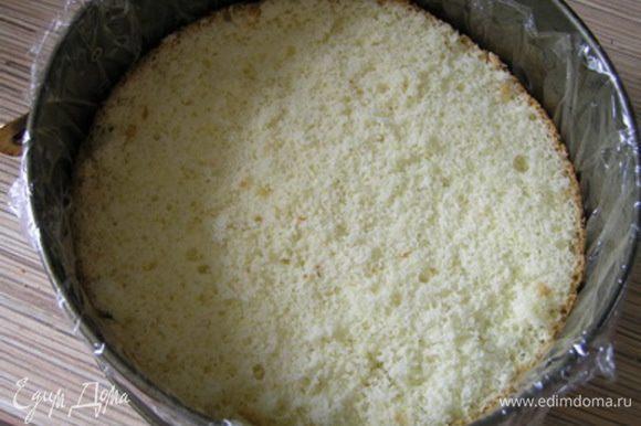 Застелить разъемную форму для торта пищевой пленкой, на дно выложить бисквитный корж.