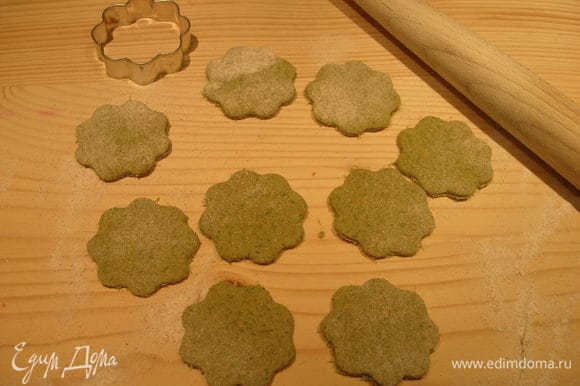 Доску посыпаем мукой, раскатываем тесто и вырезаем печенье с помощью формочек.