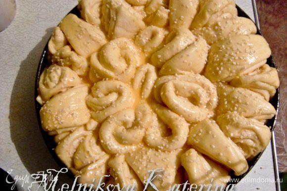 Накрыть погачу тканью и поставить в теплое и укромное место для подхода (примерно 40 минут). В отдельной тарелке смешать желток с молоком. Смазать поверхность хлеба, присыпать кунжутом.