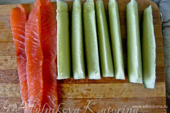 Сперва огурец необходимо разрезать на восемь равных частей. Подготовить полоски из лосося.