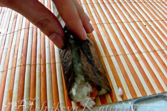 Пальцы смочить в растворе специального уксуса для суши и воды (они должны быть влажными). Край, ближний к огурцу, загнуть, формируя пальцами что-то вроде сектора.