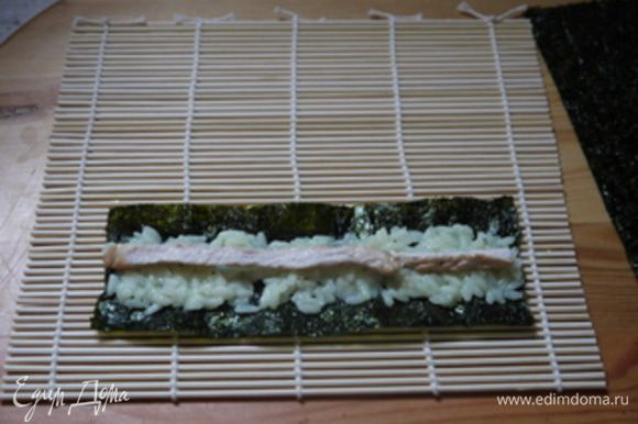 Положить в центр нори немного риса, сверху выложить полоску из куриной грудки.