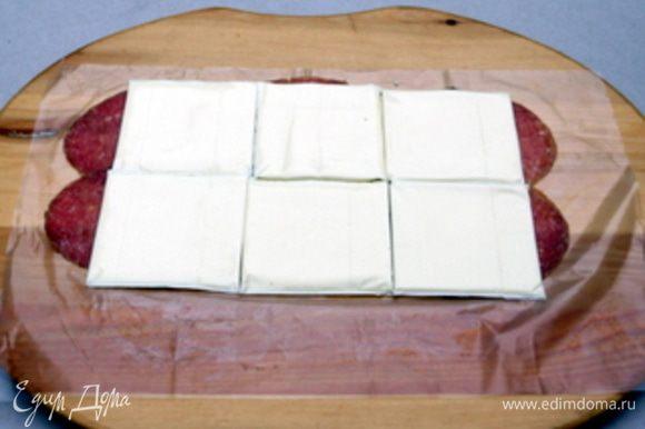 На рабочей поверхности ,накрытой пергаментом, разложить тонко нарезанные ломтики салями. Сверху на салями распределить пластинки сыра.