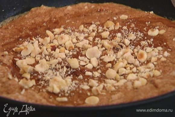 Разогреть в тяжелой сковороде сливочное масло, выложить шоколадную массу, присыпать оставшимся фундуком и готовить 2–3 минуты.