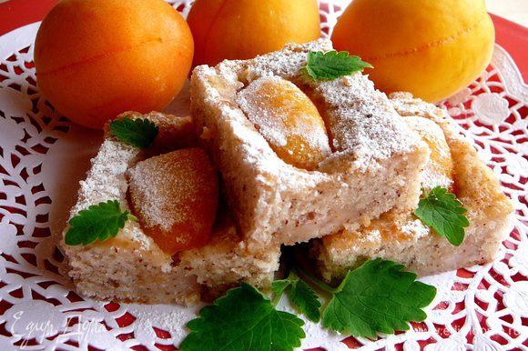 Духовку разогреть до 170 градусов. Вылить тесто в прямоугольную форму и распределить по нему кусочки абрикоса...Выпекать пирог около 30 минут до образования румяной корочки. Перед подачей нарезать на небольшие кусочки и посыпать сахарной пудрой.