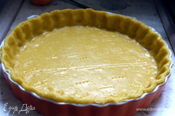 Достать охлажденное тесто и раскатать его между двух листов пергамента. Поместить тесто в форму для выпечки диаметром 24 см. Наколоть вилкой.