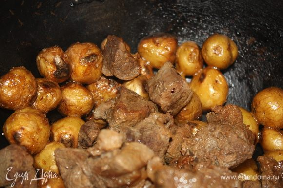 Когда картофель приготовится, добавить к нему тушеную говядину, каплю жидкого дыма и дать несколько минут еще протомиться.