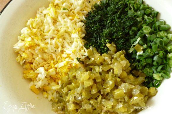 Вареные яйца натереть на крупной терке,добавить мелко нарезанную зелень лука и укропа,обжаренные огурцы и хорошо перемешать.