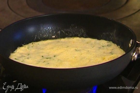Разогреть в сковороде 1 ч. ложку сливочного и 1 ч. ложку оливкового масла, влить половину яичной массы и равномерно распределить. Как только края схватятся, накрыть сковороду крышкой и убавить огонь.