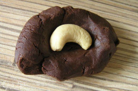 С помощью ложки набирать небольшое количество шоколадной массы, немного размять в руках, внутрь положить орешек