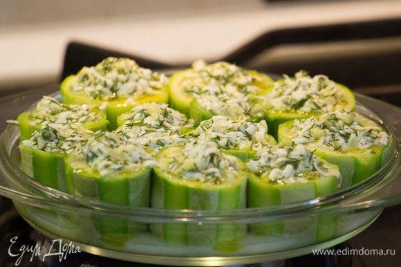 Начинить получившимся фаршем кабачки и уложить их в форму, сбрызнуть сверху оливковым маслом.