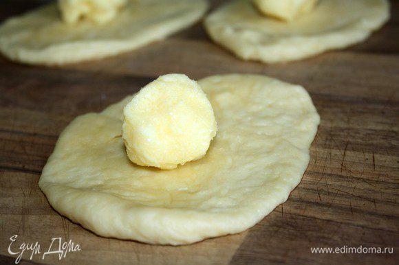 Поднявшееся тесто разделить на небольшие(50 гр)кусочки.Размять каждый из них на присыпанном мукой столе в небольшую лепёшку.Охлаждённую начинку разделить по количеству лепёшек и выложить на каждую масляный шарик.