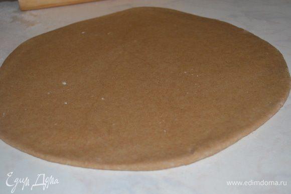 Тесто раскатать в круг толщиной примерно 1/2 см.