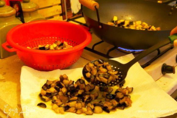 Обжарить баклажаны на большом количестве оливкового масла. Достать шумовкой из масла и перенести на блюдо, накрытое бумажными полотенцами, чтобы они впитали излишек масла.