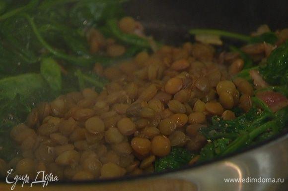 Шумовкой выложить в сковороду к шпинату готовую чечевицу, перемешать, посолить, поперчить и снять с огня.