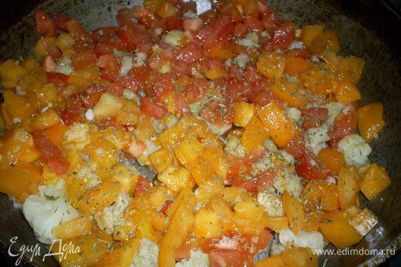 На сковороду с разогретым маслом выкладываем отваренную капусту. Сверху на нее - помидоры. Немного солим наши овощи. Можно посыпать их любимой приправой. Я посыпала Итальянскими травами, что придало блюду восхитительный аромат. Накрываем крышкой и тушим на среднем огне.