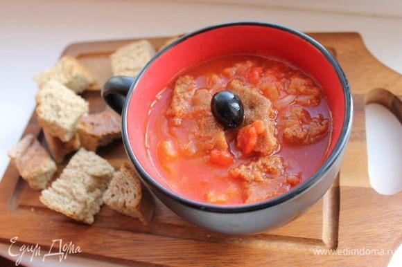 Добавить бульон с хлебом, уменьшить огонь и готовить ещё 10 минут, помешивая. Посолить, поперчить, добавить паприку, 2 столовые ложки оливкового масла. Через 5 минут суп готов. Приготовить заправку для томатного супа: смешать мелко нарезанные маслины и растолченные в ступке с 1 зубчиком чеснока листья базилика. Разложить суп по тарелкам, положить по ложке заправки, посыпать тертым сыром.