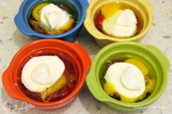 Приготовить 4 креманки. Смазать дно оливковым маслом. Мелко порубить помидоры.Выложить на дно креманок порубленные помидоры.Или, что гораздо вкуснее, влить немного соуса Наполетана от Saclà (примерно 1 см). Разбить в каждую креманку по яйцу. Посолить, поперчить. Присыпать орегано, тимьяном и базиликом. Сверху положить по кружочку моцареллы.Запечь в духовке на водяной бане (поместив в ёмкость с кипящей водой) при 200° около 7 минут. Подать с жареным хлебом.