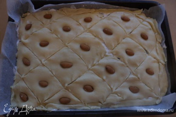 Накрыть вторым пластом теста и выложить оставшуюся начинку, и наконец накрыть третьим пластом теста (начинки на ней не должно быть). Надрезать верхний слой теста на ромбики и в каждый ромбик вложить миндаль. Сверху пирог смазать взбитым желтком. Поставить готовый пирог в разогретую до 180 градусов духовку и выпекать 45-50 минут.