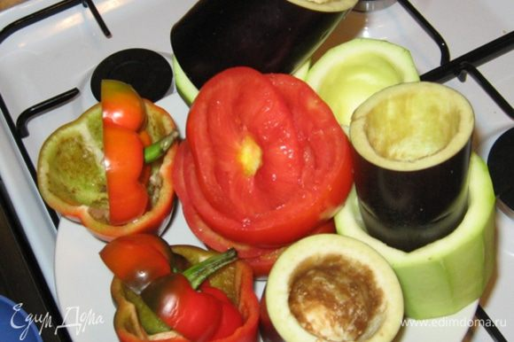 """Теперь подготовим овощи для фарширования. Начнем с баклажана. Срезаем """"попку"""" и разрезаем его поперек на высоту помидор и перцев. Аккуратно, чтобы не пробить дно, чайной ложкой удаляем сердцевину. Кабачок чистим от кожуры и подготавливаем аналогично баклажану. Теперь их надо приварить в подсоленной воде. Сначала в кипящую воду опускаем баклажан на 2 минуты, затем выкладываем к нему кабачок и буквально через минуту сливаем воду. У помидора и перца срезаем шляпки и точно также удаляем сердцевинки."""