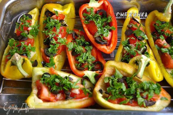 На половинки перцев укладываем дольки помидор, затем чеснок, маслины, по 2 каперса. Присыпать немного рубленой петрушкой.