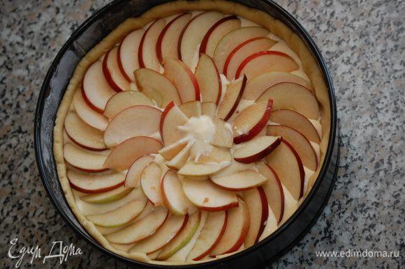 Залить тесто творожным кремом. Сверху выложить дольки яблок, слегка вдавливая их в крем.