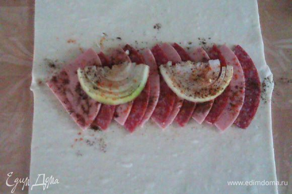 Разрезаем срез лука пополам, выкладываем сверху, посыпаем черным перцем и паприкой.