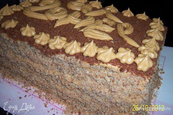 шоколадной крошкой обсыпала верх торта, остальной - бока, а оставшимся кремом я попыталась нанести название торта и по краю сделала цветочки с помощью кондитерского шприца.