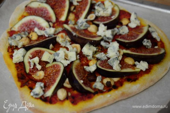 Достать пиццу (духовку не выключать), выложить на нее , нарезанный дольками инжир и сыр (предварительно разломав его на кусочки.) Отправить в духовку минут на 5 - 7.