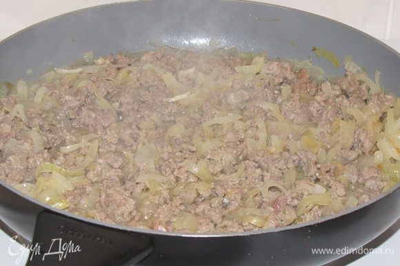 Рис промыть и оставить. Репчатый лук нарезать тонкими полукольцами и обжарить в разогретом масле, примерно 8 минут. Добавить фарш и готовить, разминая комки, пока мясо не поменяет цвет.