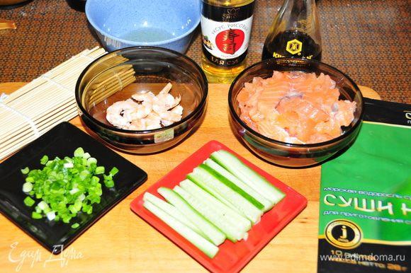Подготовим все ингредиенты: 1) Рыбу нарезать тонкими брусочками 2) Креветки окунуть в кипящую подсоленную воду на 2-3 минуты, слить, остудить и почистить 3) Огурец порезать тонкими брусочками 4) Мелко нарезать зелёный лук (достаточно несколько пёрышков) 5) В отдельную мисочку налить рисовый уксус (можно немного разбавить холодной водой) для смачивания рук