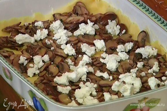 На тесто выложить половину грибов, раскрошенного мягкого козьего сыра и шпината и посыпать половиной натертого твердого козьего сыра.