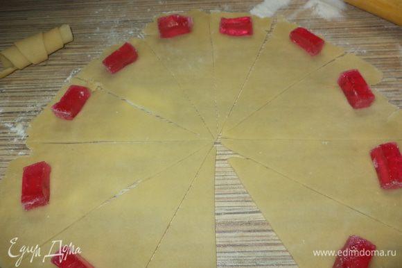 разрезать уголками на 12 частей, по краю уложить брусочки мармелада и скрутить рогалики