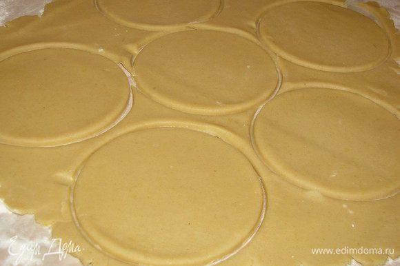 Смажьте сливочным маслом формочки для кексов. На присыпанной мукой поверхности раскатайте подготовленное тесто в тонки пласт 5 мм. Вырежьте из теста с помощью стакана или кондитерского кольца кружки чуть большего диаметра, чем формочки.