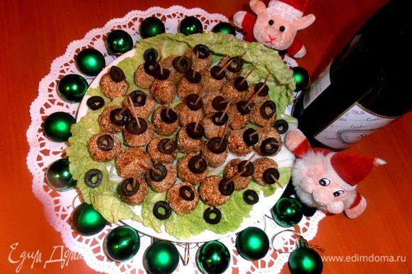 """Выкладываем """"рафаэлки"""" на листья салата, сверху на зубочистку надеваем оливку..."""