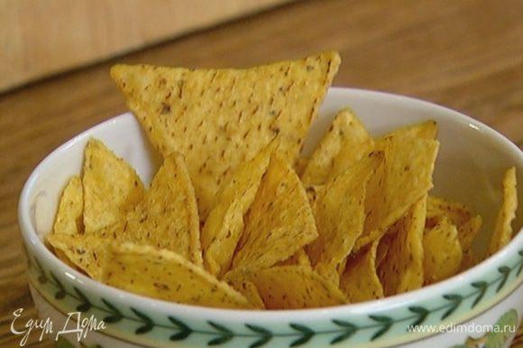 Кукурузные чипсы поломать руками на небольшие кусочки.